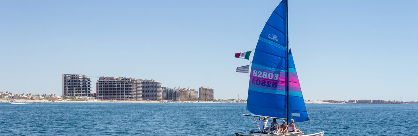 Regatta sailboat on the water with the three Las Palomas properties in the background